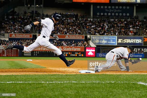 Ichiro Suzuki of the New York Yankees is safe at first base on a throwing error by third baseman Ryan Flaherty of the Baltimore Orioles in the third...