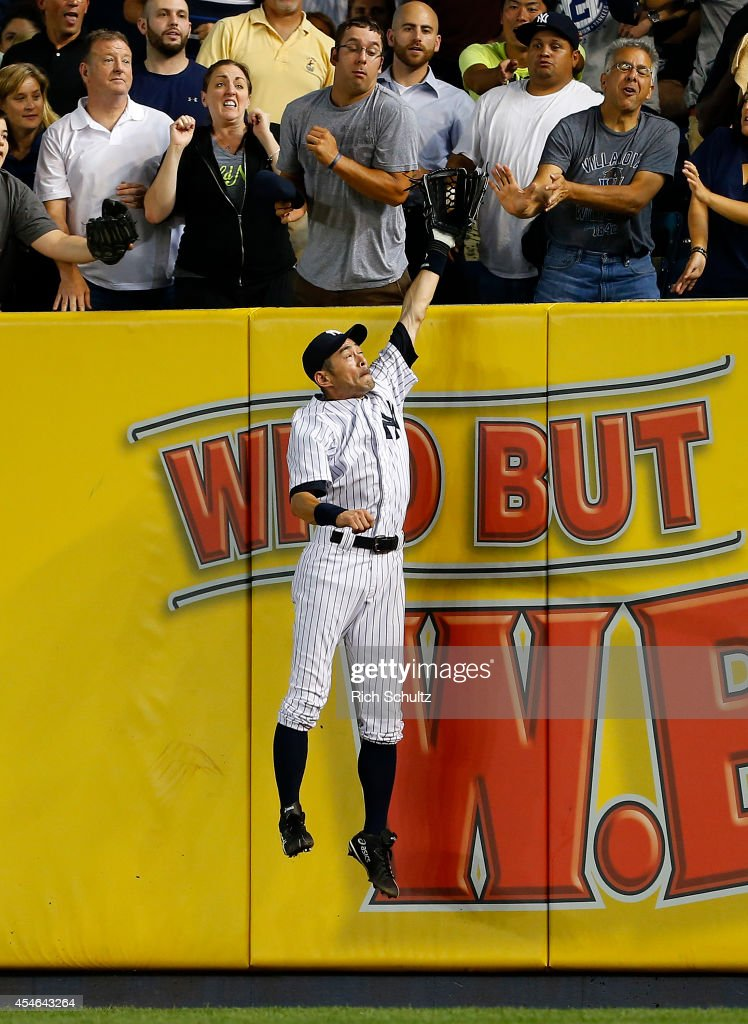 Ichiro Suzuki #31 of the New York Yankees jumps as the ball lands just behind his glove for a home run by Brock Holt #26 of the Boston Red Sox during the fifth inning in a MLB baseball game at Yankee Stadium on September 4, 2014 in the Bronx borough of New York City.
