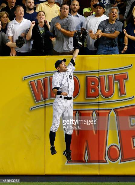 Ichiro Suzuki of the New York Yankees jumps as the ball lands just behind his glove for a home run by Brock Holt of the Boston Red Sox during the...