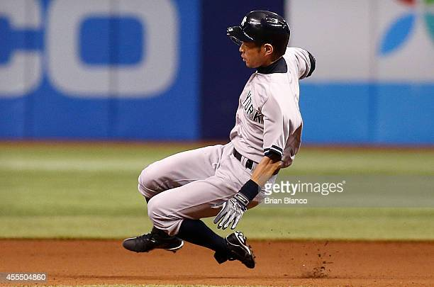 Ichiro Suzuki of the New York Yankees leaps to slide into second base after hitting a double off of pitcher Alex Colome of the Tampa Bay Rays during...