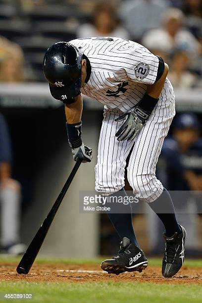 Ichiro Suzuki of the New York Yankees reacts after fouling the ball off his foot in the seventh inning against the Tampa Bay Rays at Yankee Stadium...