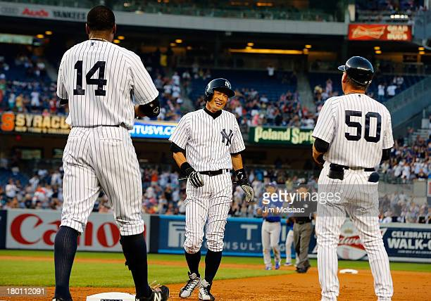 Ichiro Suzuki of the New York Yankees reacts after his first inning base hit against the Toronto Blue Jays with teammate Curtis Granderson and first...