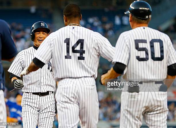 Ichiro Suzuki of the New York Yankees reacts to his teammates including Curtis Granderson and first base coach Mick Kelleher pouring onto the field...