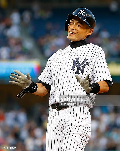 Ichiro Suzuki of the New York Yankees reacts to his teammates pouring onto the field after hitting a single his 4000 career hit in the first inning...