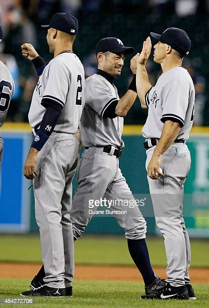 Ichiro Suzuki of the New York Yankees receives hight-fives from Derek Jeter and manager Joe Girardi after a 8-4 win over the Detroit Tigers at...
