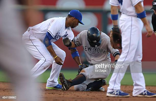 Ichiro Suzuki of the New York Yankees slides safely into second past the tag of Alcides Escobar of the Kansas City Royals as he advanced on a...
