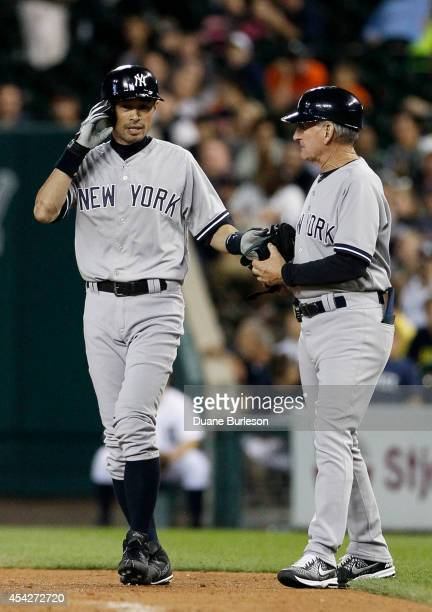 Ichiro Suzuki of the New York Yankees talks with first base coach Mick Kelleher after hitting a single against the Detroit Tigers during the ninth...