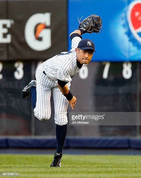 Ichiro Suzuki of the New York Yankees throws the ball back into the infield during the second inning against the Boston Red Sox at Yankee Stadium on...