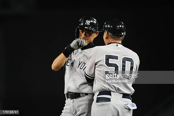 Ichiro Suzuki of the New York Yankees waits at first base with coach Mike Kelleher during the game against the Los Angeles Dodgers at Dodger Stadium...