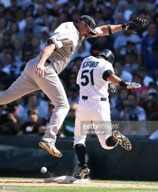 Ichiro Suzuki of the Seattle Mariners beats out an infield bunt single against first baseman Jason Giambi of the New York Yankees on September 7,...