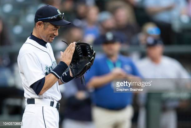 Ichiro Suzuki of the Seattle Mariners claps after catching the ceremonial pitch before a game against the New York Yankees at Safeco Field on...