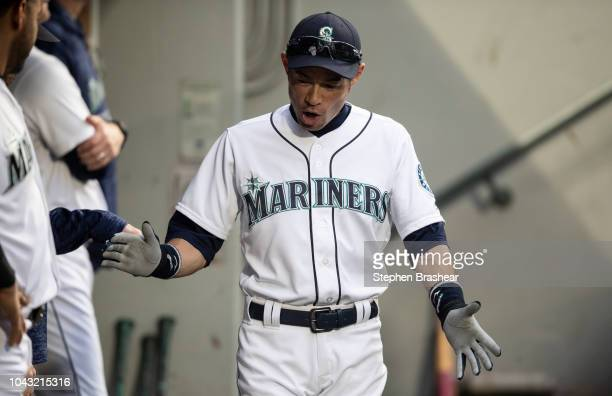 Ichiro Suzuki of the Seattle Mariners claps his hands as he walks through the dugout before a game against the Texas Rangers at Safeco Field on...