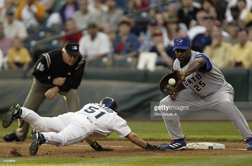 Ichiro Suzuki #51 of the Seattle Mariners dives back to first base on a pickoff attempt as Carlos Delgado #25 of the Toronto Blue Jays catches the ball during the game on August 13, 2003 at Safeco Field in Seattle, Washington. The Mariners defeated the Blue Jays 13-6.