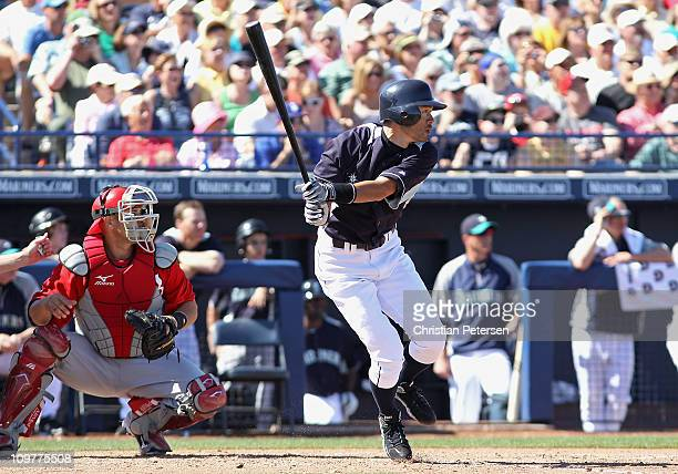Ichiro Suzuki of the Seattle Mariners hits a RBI sacrafice fly against the Cincinnati Reds during the third inning of the spring training game at...