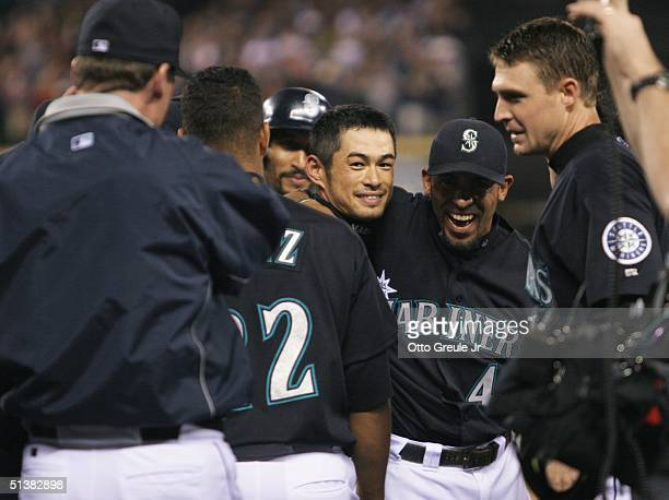 Ichiro Suzuki of the Seattle Mariners is congratulated by teammates after singling to center field against the Texas Rangers in the third inning on...