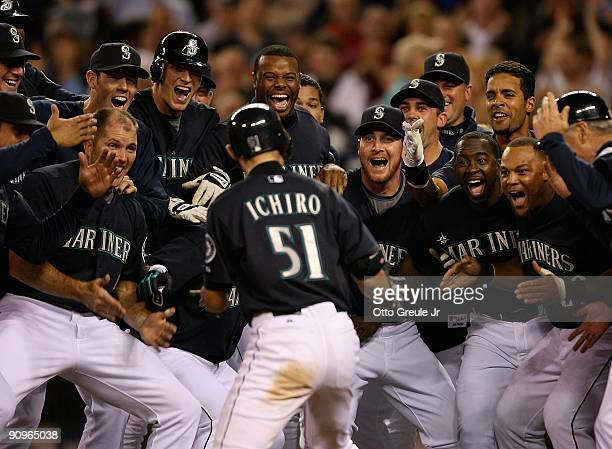 Ichiro Suzuki of the Seattle Mariners is mobbed by teammates after hitting a game winning tworun homer in the bottom of the ninth inning to defeat...