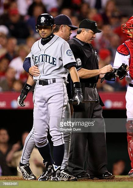 Ichiro Suzuki of the Seattle Mariners is restrained by coach Mike Goff during an argument with home plate umpire Dana DeMuth during the game with the...