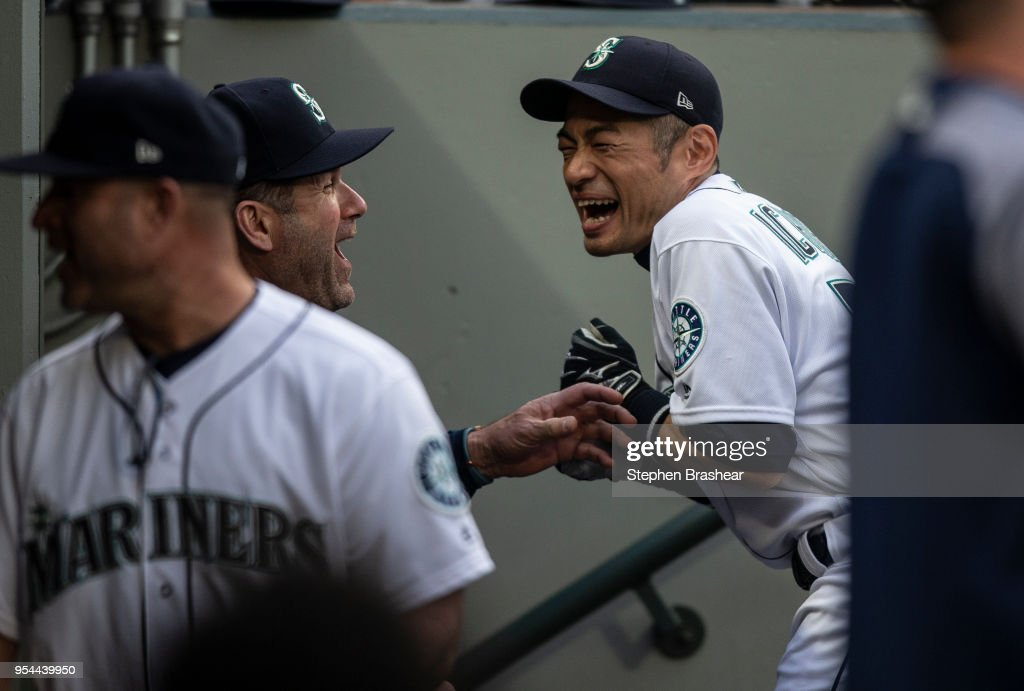Ichiro Suzuki #51 (R) of the Seattle Mariners jokes with hitting coach Edgar Martinez in the dugout before a game against the Oakland Athletics at Safeco Field on May 3, 2018 in Seattle, Washington. The Mariners announced before the game that Ichiro would transition out of a playing role for 2018 and into the front office as a special assistant to the chairman, effective today. Ichiro's agent said that the 10-time All-Star is not retiring, leaving open the possibility of returning to the field in 2019, according to published reports.