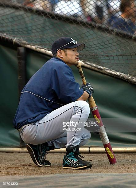 Ichiro Suzuki of the Seattle Mariners kneels beside the batting cage while waiting for his turn to hit prior to the Mariner's game against the Texas...