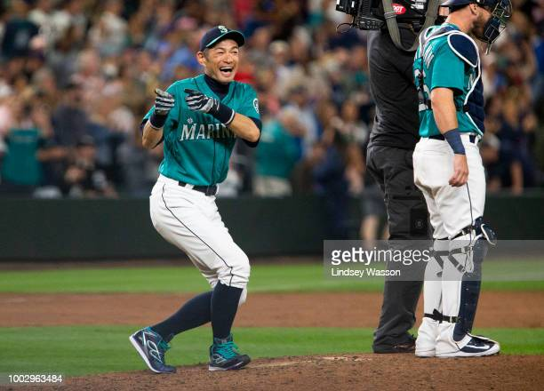 Ichiro Suzuki of the Seattle Mariners laughs after imitating a pitcher's stance on the mound as the team celebrates their win at Safeco Field on July...