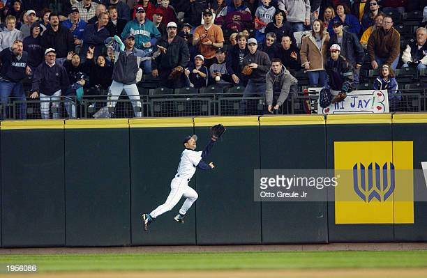 Ichiro Suzuki of the Seattle Mariners makes a leaping catch for the second out of the eighth inning off the bat of Terrence Long of the Oakland...