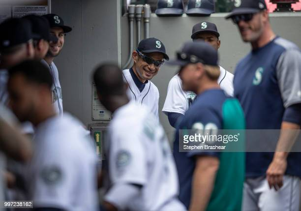 Ichiro Suzuki of the Seattle Mariners peaks around from the entrance of the clubhouse into the dugout before a game against the Colorado Rockies at...