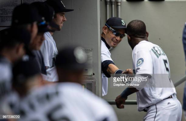Ichiro Suzuki of the Seattle Mariners shakes hands with Guillermo Heredia of the Seattle Mariners from the entrance to the clubhouse before a game...