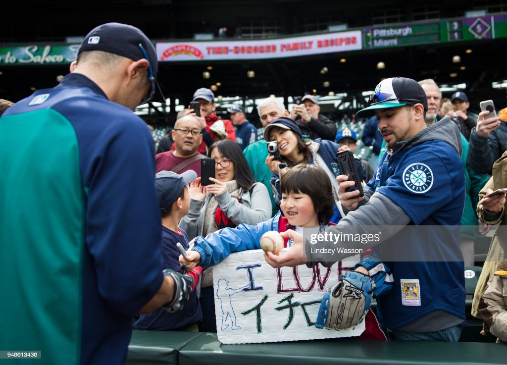 Ichiro Suzuki #51 of the Seattle Mariners signs autographs for a young fan with an 'I love Ichiro' sign before the game against the Oakland Athletics at Safeco Field on April 15, 2018 in Seattle, Washington.