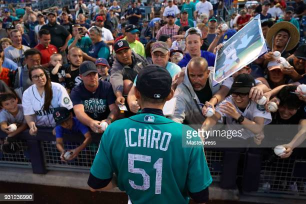 Ichiro Suzuki of the Seattle Mariners signs autographs for fans during a spring training game between Seattle Mariners and Chicago White Sox on March...