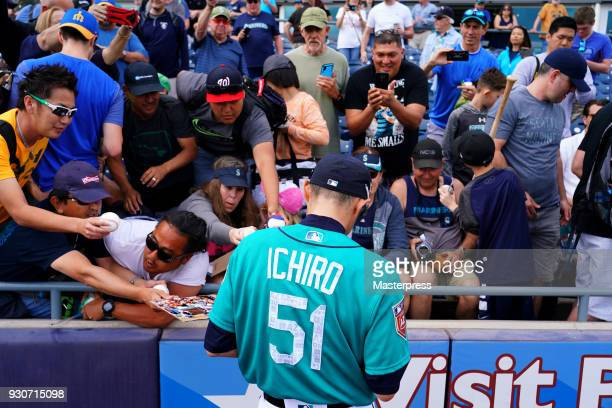 Ichiro Suzuki of the Seattle Mariners signs autographs for fans prior to the spring training game against Cincinnati Reds on March 11 2018 in Peoria...