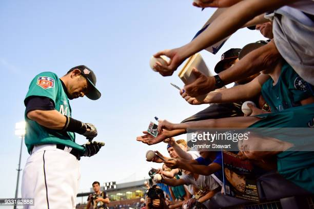 Ichiro Suzuki of the Seattle Mariners signs autographs for fans prior to the spring training game against the Chicago White Sox at Peoria Sports...