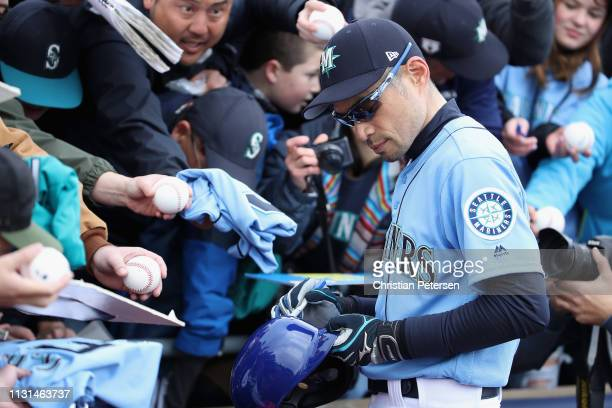 Ichiro Suzuki of the Seattle Mariners signs autographs for fans before the MLB spring training game against the Oakland Athletics at Peoria Stadium...