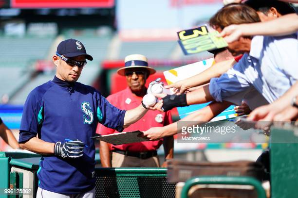 Ichiro Suzuki of the Seattle Mariners signs autographs for fans during the MLB game against the Los Angeles Angels at Angel Stadium on July 10 2018...
