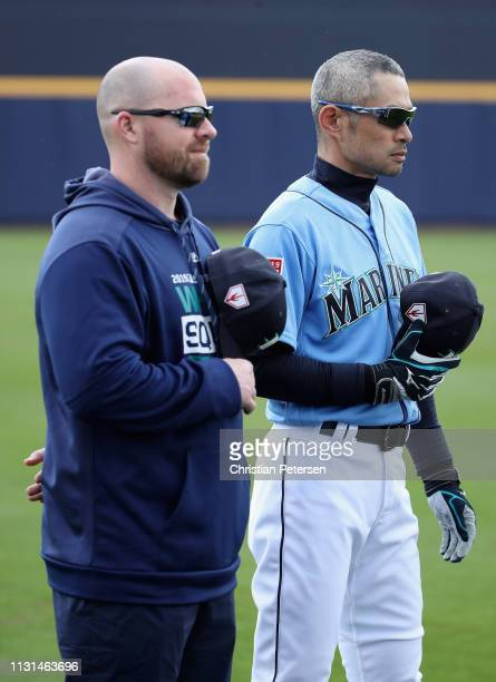 Ichiro Suzuki of the Seattle Mariners stands attended for the national anthem before the MLB spring training game against the Oakland Athletics at...