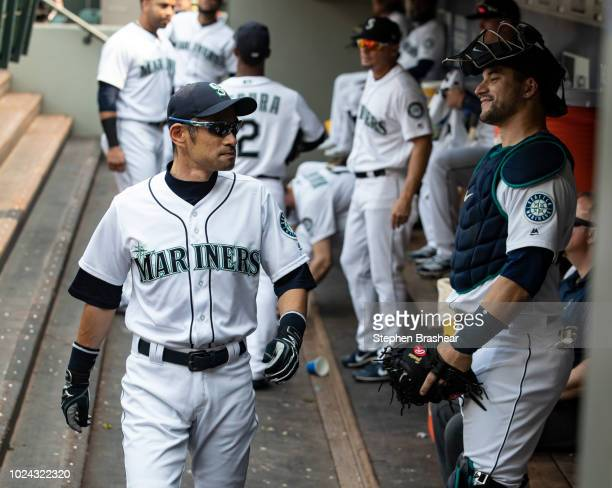 Ichiro Suzuki of the Seattle Mariners walks through the dugout past Mike Zunino of the Seattle Mariners before a game against the Houston Astros at...