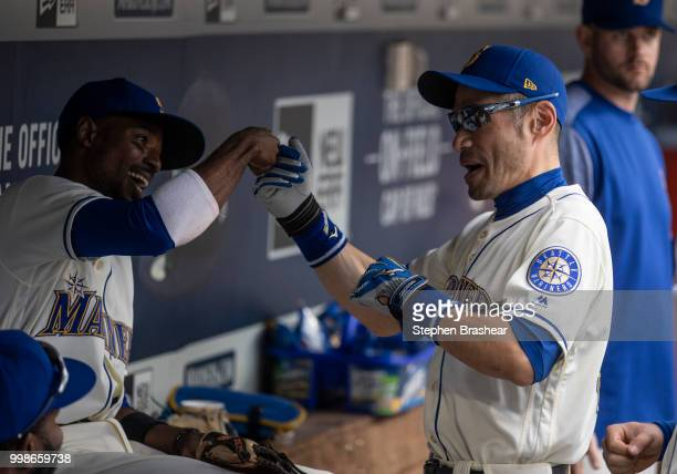Ichiro Suzuki right of the Seattle Mariners jokes with Dee Gordon of the Seattle Mariners in the dugout before a game against the Colorado Rockies at...