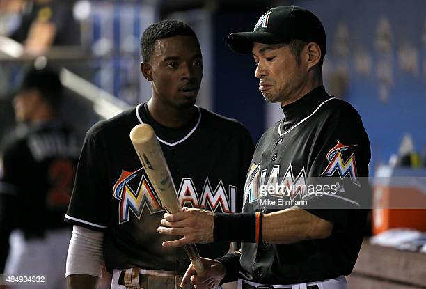 Ichiro Suzuki talks with Dee Gordon of the Miami Marlins after scoring during a game against the Philadelphia Phillies at Marlins Park on August 22,...
