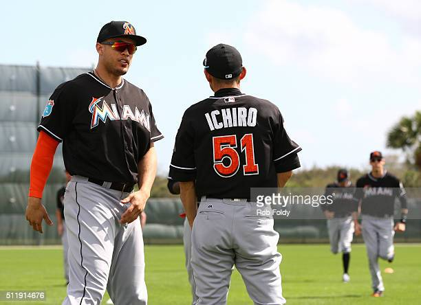 Ichiro Suzuki talks with Giancarlo Stanton during a Miami Marlins workout on February 23 2016 in Jupiter Florida
