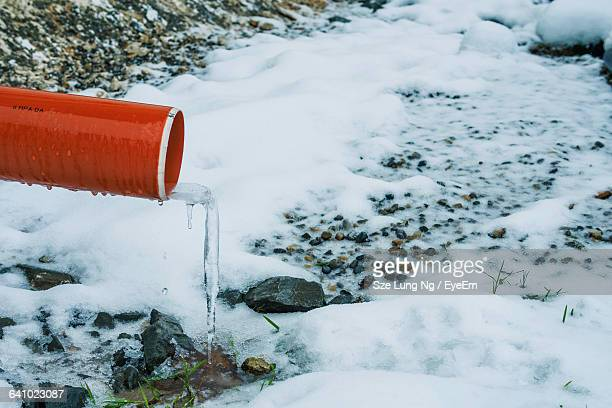 Icicle Hanging From Pipe Over Stream