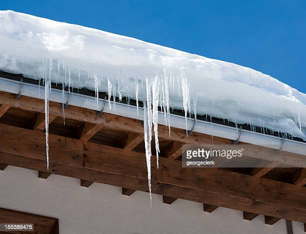 icicles and snow overhanging a roof - eaves stock photos and pictures