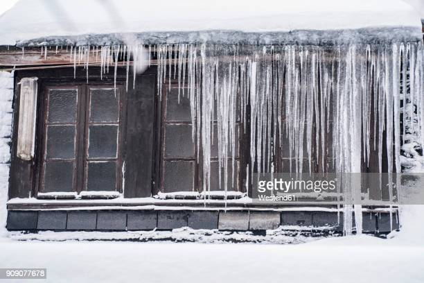 icicles hanging down from a roof top in winter - 深い雪 ストックフォトと画像