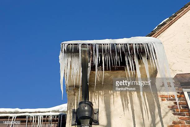 Icicles Hanging from a Mansion Roof against Clear Blue Sky