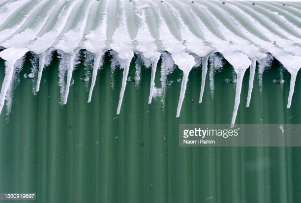 icicles hanging off green tin roof in winter - clima alpino foto e immagini stock