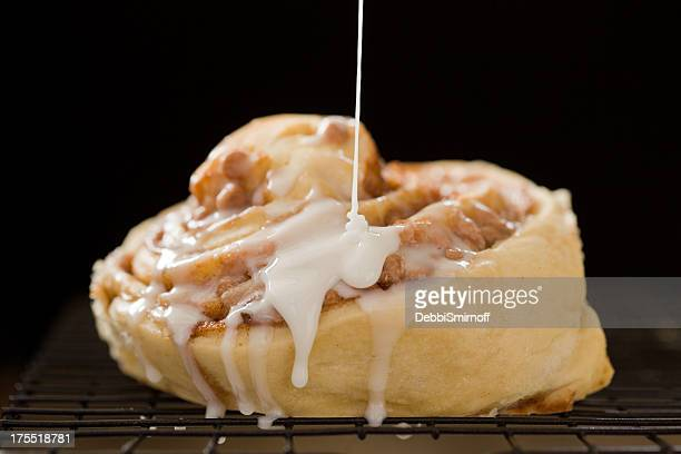icing a homemade cinnamon roll - icing stock pictures, royalty-free photos & images