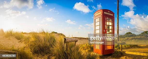 Iconic british red telephone box in idyllic summer beach dunes