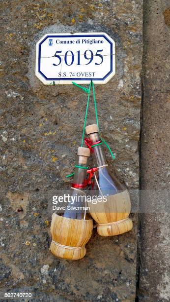 Iconic chianti bottles decorate a street sign on July 22 2015 in the medieval village of Pitigliano in the Grosseto province of Tuscany Italy Tuscany...