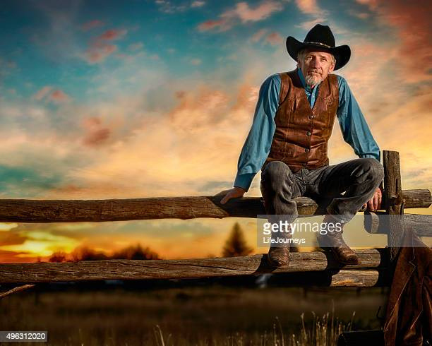 Iconic Cowboy Sitting On A Rail Fence In The Sunset