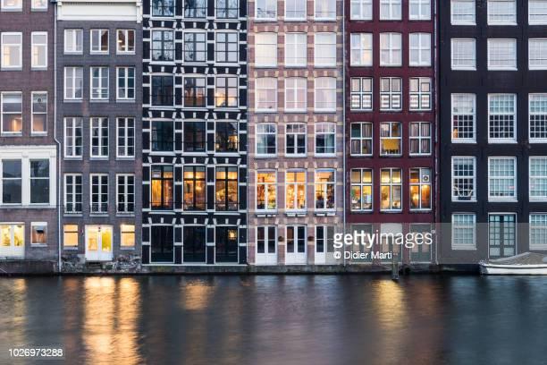 iconic dutch houses facade by canal in amsterdam - fachada arquitectónica fotografías e imágenes de stock