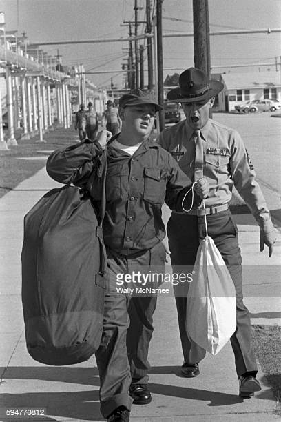 Iconic image of a Marine drill instructor wearing a fabled campaign hat berates a recruit lagging behind the rest of the recruits platoon carrying a...