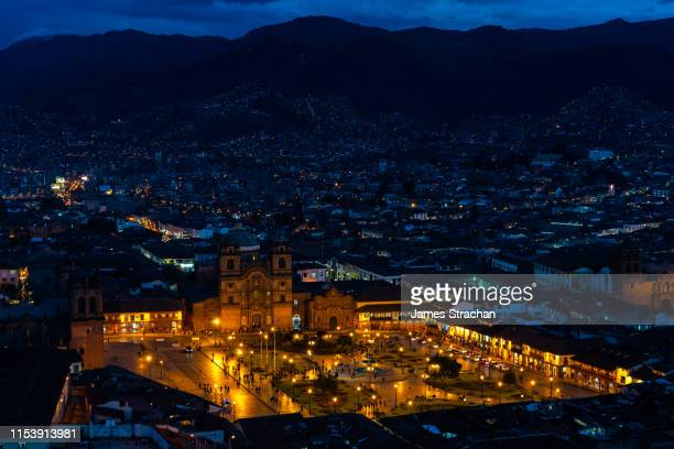 iconic main square, plaza de armas, illuminated at night and set against the surrounding city and hills beyond, cusco, unesco world heritage site, sacred valley, peru - james strachan stock pictures, royalty-free photos & images